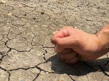 Cracked ground and angry fist hand Royalty Free Stock Photography