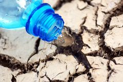 Cracked ground with empy bottle. When water depletes the ground is cracked stock photos