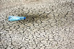 Cracked ground with empy bottle. When water depletes the ground is cracked Royalty Free Stock Image
