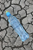 Cracked ground with water in a bottle.  Stock Image