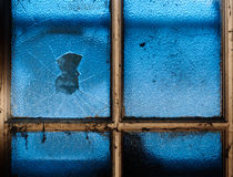 Cracked hole in old grungy window. Broken hole in an old frosted window with light shining across Royalty Free Stock Photos