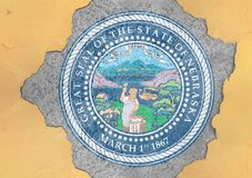 Cracked hole with US state Nebraska seal flag abstract in facade. Structure big damaged concrete stock images