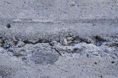 The Cracked House Foundation. Cracked concrete foundation with small rocks embedded in it. Light gray tones. Background. Horizontal Royalty Free Stock Photo