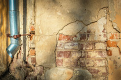 Cracked house wall with hanging metal drainpipe. Royalty Free Stock Photography