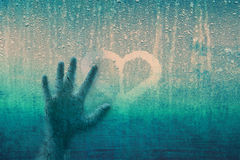 Cracked human hand on window with heart sign. Grunge cracked human hand on droplet rainy glass window with love heart symbol. Conceptual love breakup image Stock Image