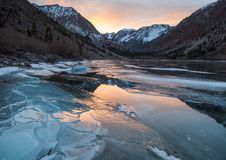 Cracked ice on a frozen lake captures sunset light. In the Sierra Nevada stock photo
