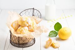 Cracked Lemon cookies in small metal basket on white table backg Royalty Free Stock Photography