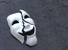 Cracked Mask. Broken Mask on asphalt surface. Concept image royalty free illustration