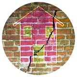 Cracked old and aged brick wall with a colored house drawn on it - Round icon concept image - Photography in a circle.  stock photography