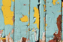 Cracked old paint on wooden boards. Turquoise and yellow royalty free stock photo
