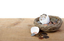 A cracked open egg with coins spilling out Royalty Free Stock Images