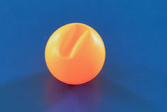 A cracked orange ping pong ball. A cracked 40mm large white and orange ping pong (table tennis) ball with blue background Royalty Free Stock Images