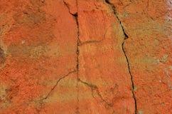 Cracked orange wall Stock Images