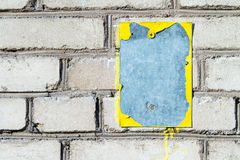Cracked painted metal plate on brick wall Stock Photos