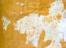 Cracked painted yellow concrete wall background Stock Images