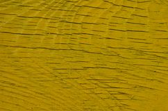 Cracked wood texture painted in yellow. Close up of the weathered wood board painted in yellow with multiple micro cracks Stock Photo