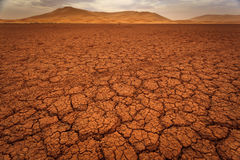Cracked pattern of dry lake bed and sand dunes Stock Photography