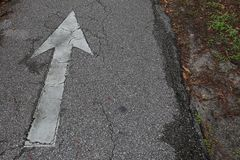 White Distressed Arrow on Asphalt Bike Trail royalty free stock image