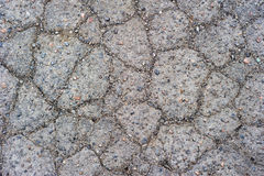 Cracked Pavement. A close up on old cracked pavement with little stones and debris royalty free stock photography