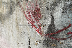 Cracked peeled red grey black paint on old damaged wall Royalty Free Stock Image
