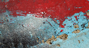 Cracked peeled red and turquoise paint on old damaged wall Stock Photo