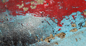 Cracked peeled red and turquoise paint on old damaged wall Stock Image
