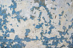Cracked and peeling paint. A view of a wall with peeling white paint that is revealing a previous coat of blue paint Stock Photo