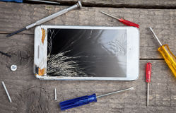 Cracked phone glass. On wooden background Royalty Free Stock Image