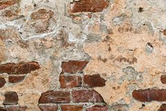 Cracked plaster on the brick wall royalty free stock images