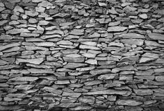 Cracked real stone wall surface with cement in black and white t Royalty Free Stock Photos