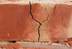 Cracked red brick. Closeup of cracked red brick Stock Images