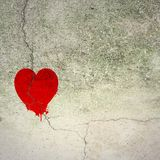 Cracked red heart on concrete wall Royalty Free Stock Image
