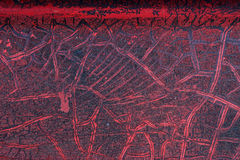 Cracked red paint on grunge metal surface - macro 6. Close up,macro photography of cracked red paint on grunge metal rough surface - small part of an old dirty Stock Image
