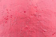 Cracked red paint texture. Close-up of old painted red wall. Abstract grunge background. Vintage scratched surface Royalty Free Stock Photo