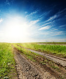 Cracked road in green grass at sunset in a blue sky Royalty Free Stock Photos