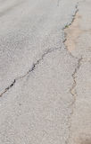 Cracked road and potholes in pavement of a street Royalty Free Stock Image