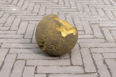 Cracked Rock Ball on Street. Cracked Moss Rock Ball on Patterned Brick Floor royalty free stock images