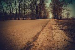 Cracked Rural Road Filtered. Old cracked, damaged asphalt road in countryside, vintage colors Royalty Free Stock Image