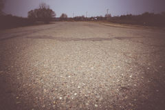 Cracked Rural Road Filtered. Old cracked, damaged asphalt road in countryside, vintage colors Royalty Free Stock Photos