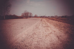 Cracked Rural Road Filtered. Old cracked, damaged asphalt road in countryside, vintage colors Stock Photography