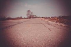 Cracked Rural Road Filtered. Old cracked, damaged asphalt road in countryside, vintage colors Stock Image