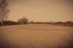 Cracked Rural Road Filtered. Old cracked, damaged asphalt road in countryside, vintage colors Royalty Free Stock Photography