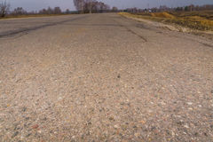 Cracked Rural Road. Old cracked, damaged asphalt road in countryside Stock Photos