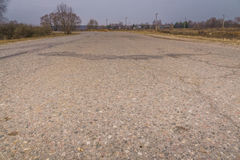 Cracked Rural Road. Old cracked, damaged asphalt road in countryside Stock Photo