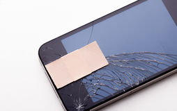 Cracked screen with sticky plaster Royalty Free Stock Images