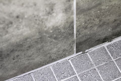 Cracked Shower Wall Corner Grout. Gray tile grout in a home shower that has broken apart and needs repair. Cracked and split grout in a house shower corner stock photo