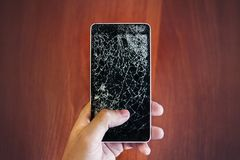 Cracked smartphone in hand holding. stock photography