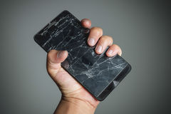 Cracked smartphone screen on hand holding. Stock Images