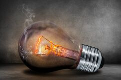 Cracked and smoking light bulb Royalty Free Stock Image