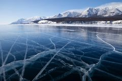 Cracked smooth surface of frozen lake Baikal in winter royalty free stock images